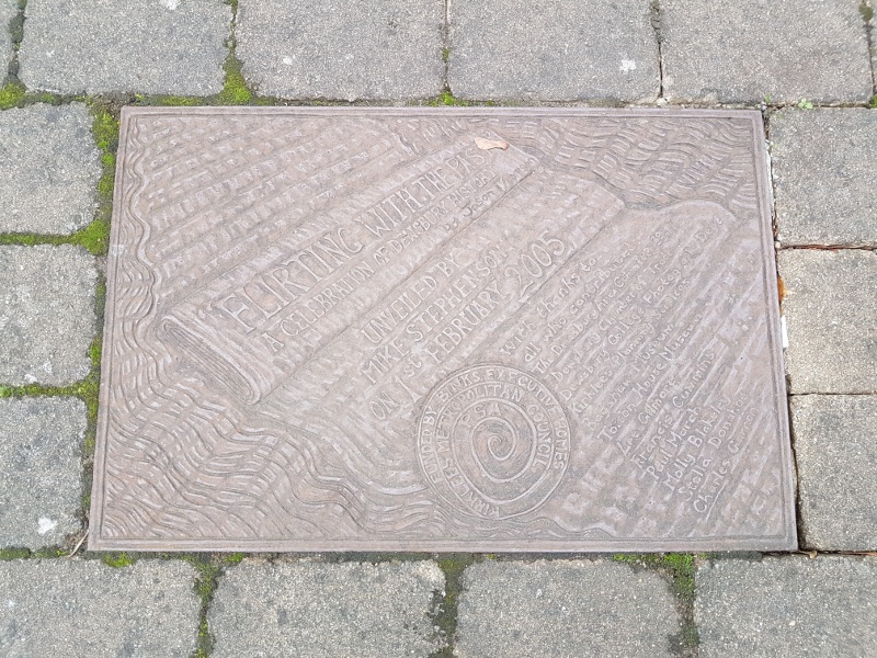 photo of the commemorative slab let into the paving next to the pair of Flirting with the Past statues in Dewsbury